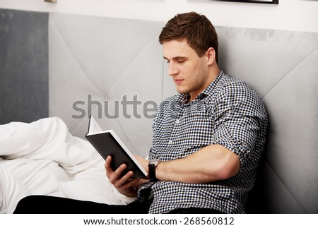 Handsome thoughtful man reading a note in his bed. - stock photo