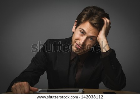 Handsome thoughtful man sitting with his head on his hand looking at the camera with a contemplative look - stock photo