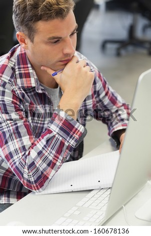 Handsome thoughtful student using computer taking notes in computer room at college - stock photo