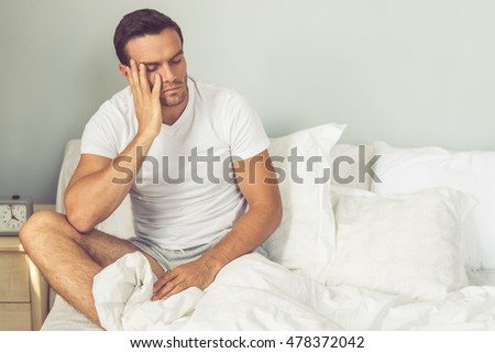 Handsome tired man in white t-shirt is leaning on his hand and sitting with closed eyes on his bed while getting up in the morning