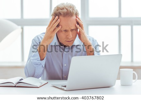 Handsome tired middle aged businessman in classic shirt is using a laptop and keeping hands on head while working in office