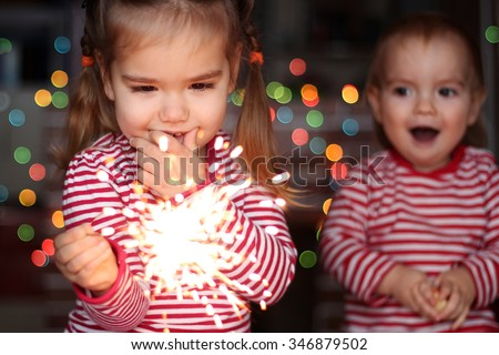 Handsome toddler boy and cute small girl in Santa hat hold burning sparkler and smile happily over defocused Christmas background - stock photo