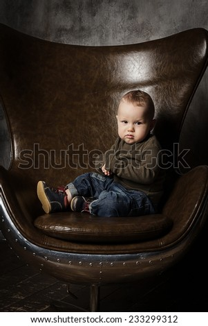 Handsome toddler in an egg armchair