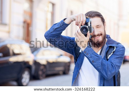 Handsome tourist is standing and photographing town. He is holding camera and smiling. The man is looking forward with interest. Copy space in left side - stock photo