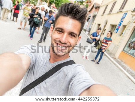 Handsome tourist taking a selfie at vacation. Young man smiling at the camera in a urban scene. Caucasian people. Concept about people, lifestyle and technology - stock photo