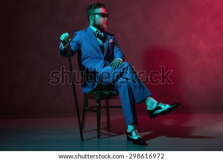 Handsome trendy old-fashioned dandy with a beard and sunglasses sitting in a chair holding his cane, red toned lighting in darkness with copyspace - stock photo