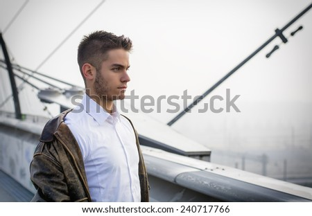 Handsome trendy young man standing on a sidewalk wearing a fashionable jacket and scarf in a relaxed confident pose looking away to a side