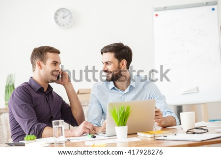 Handsome two businessmen are discussing their project - stock photo