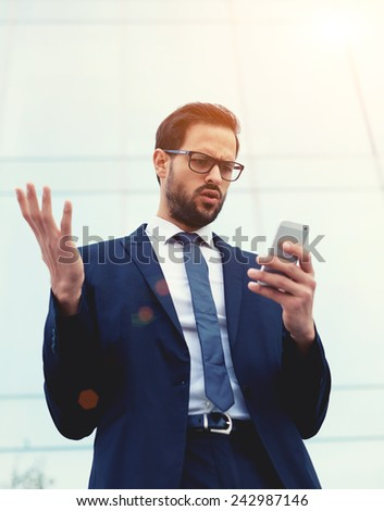 Handsome unhappy, surprised and shocked executive looking at smart phone receiving bad news, negative human emotions, facial expression, reaction - stock photo