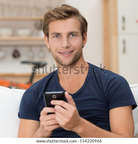 Handsome unshaven casual young man holding a smartphone in his hands and looking at the camera with a smile, indoors portrait - stock photo