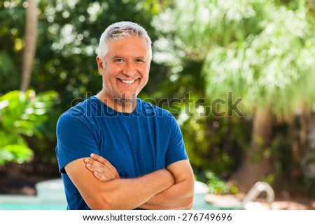 Handsome unshaven middle age man outdoor portrait with a green background. - stock photo