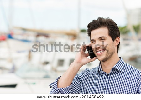 Handsome unshaven young man chatting on a mobile phone smiling at the conversation against a small boat harbour background - stock photo
