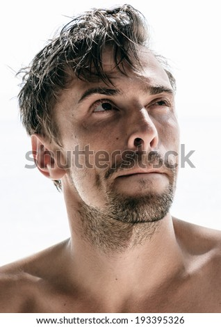 Handsome unshaven young man squinting and pursing his lips in thought as he stares pensively up into the air as he tries to weigh up a decision, isolated on white - stock photo