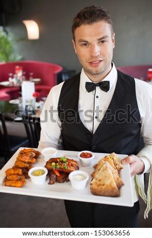 Handsome waiter serving appetizing finger food platter in classy restaurant - stock photo