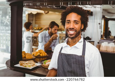 Handsome waiter smiling at camera at the coffee shop - stock photo
