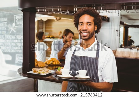 Handsome waiter smiling at camera holding tray at the coffee shop - stock photo