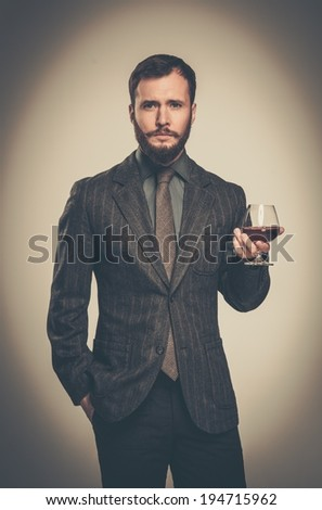 Handsome well-dressed man in jacket with glass of beverage - stock photo