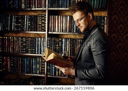Handsome well-dressed man stands by bookshelves in a room with classic interior. Fashion. - stock photo
