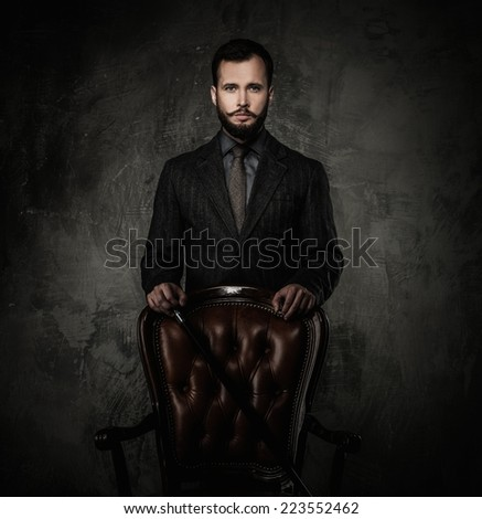 Handsome well-dressed man with walking stick standing near leather chair  - stock photo