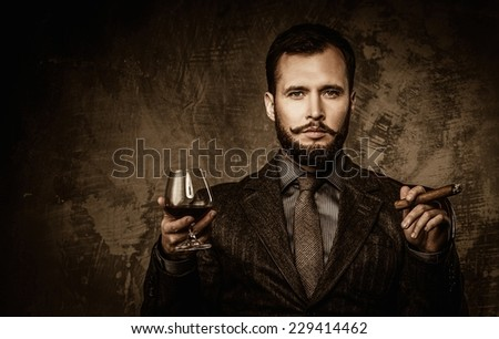Handsome well-dressed with glass of beverage and cigar - stock photo