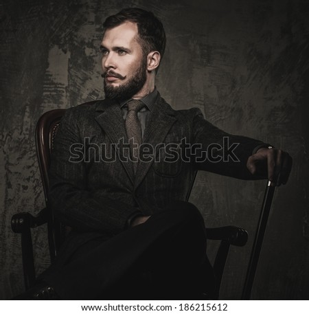 Handsome well-dressed with stick sitting in leather chair  - stock photo