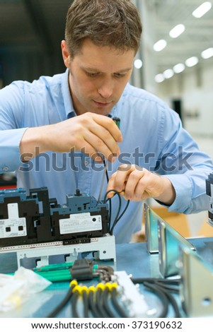 Handsome worker assembling electronic components at the factory. - stock photo