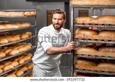 Handsome worker in uniform carrying shelves with bread at the bakery manufacturing - stock photo