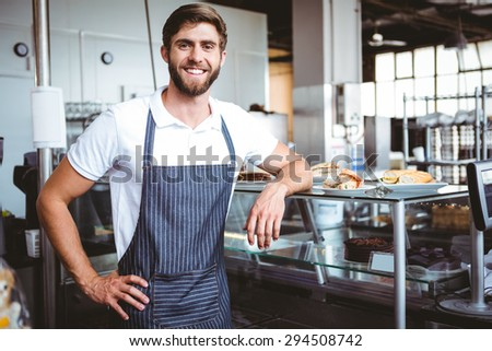 Handsome worker posing on the counter at the bakery - stock photo