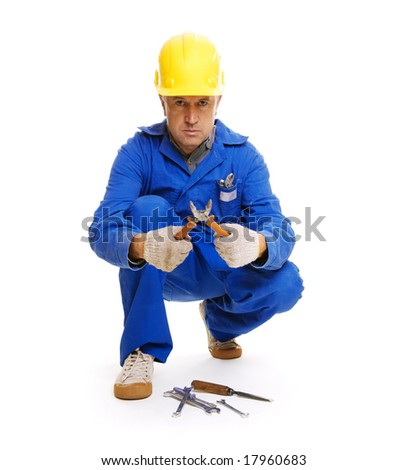 handsome workman sitting on the floor with different tools. isolated on white - stock photo