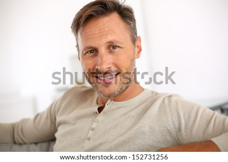 Handsome 40-year-old man relaxing in sofa - stock photo