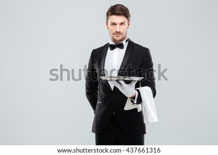 Handsome yong waiter in tuxedo and gloves holding empty tray and napkin - stock photo