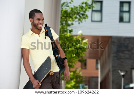 Handsome young African American male student leaning up against the wall and smiling. He is holding a skateboard and bag. - stock photo