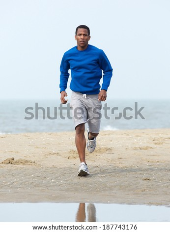 Handsome young african american man jogging at beach. Healthy lifestyle - stock photo