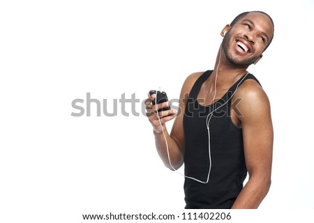 Handsome young African American man listening and smiling to music on his mobile device and looking behind - stock photo