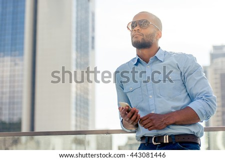 Handsome young Afro American businessman in sun glasses is holding a smartphone, looking away and thinking while standing outdoors - stock photo