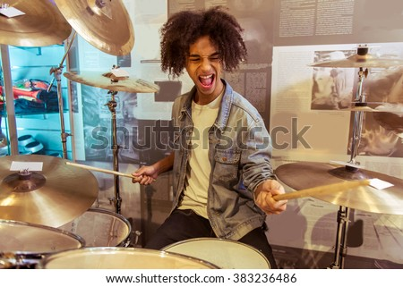 Handsome young Afro-American man in jeans jacket smiling while playing drums in a musical shop - stock photo