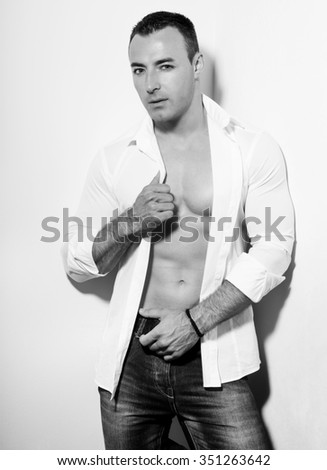 handsome young and fit bodybuilder posing with open shirt