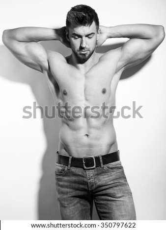 handsome young and fit bodybuilder with toned body on grey background