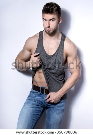 handsome young and fit bodybuilder with toned body posing on grey background in casual clothes