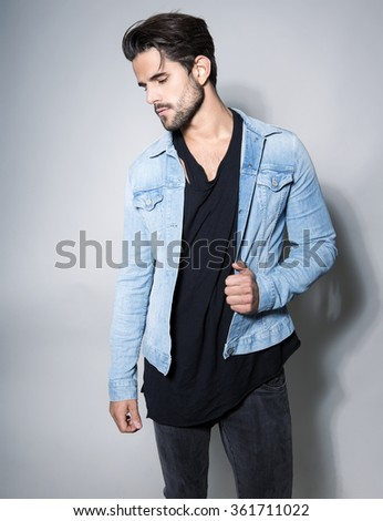 handsome young and fit man posing in casual clothes, wearing jeans jacket - stock photo