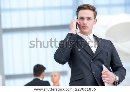 Handsome young and motivated businessman solves his business issues on the phone, while waiting for his colleagues with tablet - stock photo