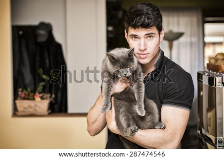 Handsome Young Animal-Lover Man Inside the House, Hugging his Gray Domestic Cat Pet. - stock photo
