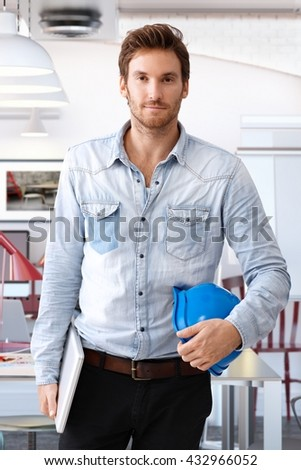 Handsome young architect holding hardhat and laptop computer, looking at camera. - stock photo