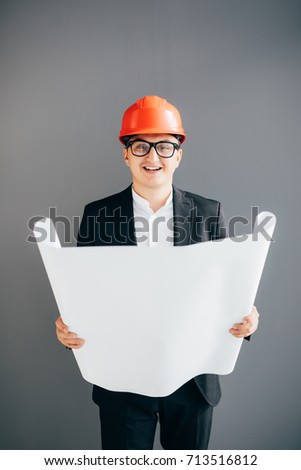 Handsome young architect in protective helmet is studying draft, on gray background