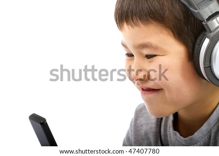 Handsome young asian boy listening to his MP3 player and smiling isolated on white background