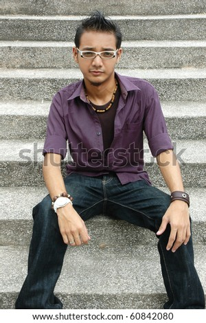 Handsome young Asian male with spectacles sitting on stairs