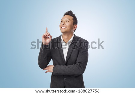 handsome young asian man pointing up with finger - stock photo