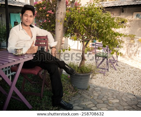 Handsome Young Asian Man Relaxing At Table In The Garden Drinking A Cup Of Coffee