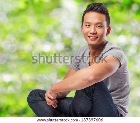 handsome young asian man sitting at park - stock photo