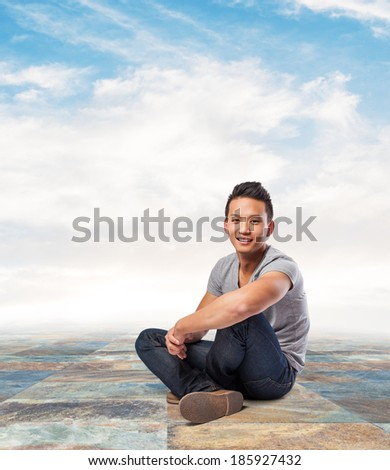 handsome young asian man sitting on the street - stock photo